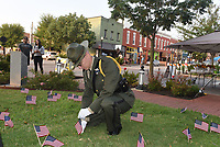 Deputy Michael Dowdle with the Benton County Sheriff's Office Honor Guard on Saturday Sept. 11 2021 places a 9-11 remembrance flag on the courthouse lawn, along with other flags placed by people who attended the 9-11 remembrance ceremony on the Bentonville square. Go to nwaonline.com/210912Daily/ to see more photos.<br />(NWA Democrat-Gazette/Flip Putthoff)