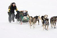 In first place Jeff Kings runs up bank from Yukon River into Kaltag during 2006 Iditarod Western AK