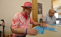 Jerry Tygard (cq) (left) and Tommy Eldridge check their bingo cards Monday, July 19, 2021,  during play at the Fayetteville Senior Activity and Wellness Center. Tygard said he likes to dye his beard for different events and Holidays. His red, white and blue beard is for the Fourth of July. The center offers bingo on Mondays and Thursdays. Check out nwaonline.com/210720Daily/ and nwadg.com/photos for a photo gallery.(NWA Democrat-Gazette/David Gottschalk)