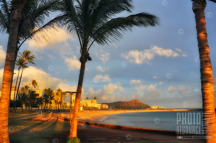 Last rays of the setting sun light up Diamond Head and Waikiki, as seen from Magic Island, Ala Moana Beach Park, O'ahu.