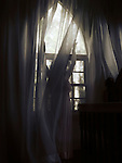 Artistic dramatic photo of a young woman in a dress standing behind the curtain by a window in a dark room of a house Image © MaximImages, License at https://www.maximimages.com