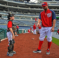 16 May 2012: Washington Nationals first baseman Adam LaRoche's son Drake LaRoche gets tips from catcher Jesus Flores during batting practice prior to a game against the Pittsburgh Pirates at Nationals Park in Washington, DC. Adam notched his 1000th career hit and was named Player of the Game as the Nationals defeated the Pirates 7-4 in the first game of their 2-game series. Mandatory Credit: Ed Wolfstein Photo