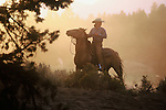 Cowgirl horseback in the dust and sunlight on a ranch in Oregon USA.