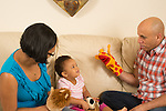18 month old toddler girl at home with parents playing with puppets