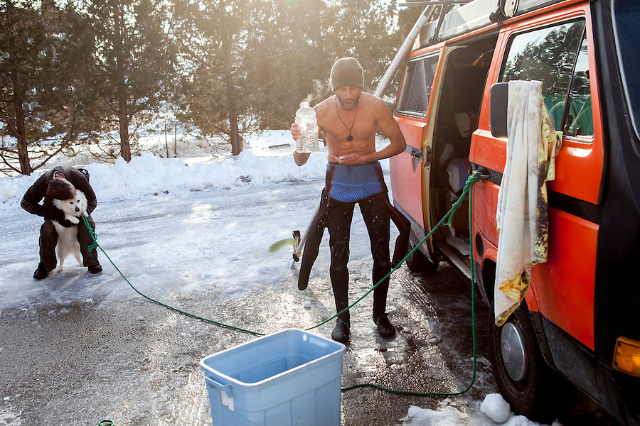 Mark Kielpinski, of Brewster, MA, pours hot water down his wetsuit after surfing at Green Harbor in Marshfield, MA, on a cold February day.  At left, a fellow surfer snuggles his dog, Mack.