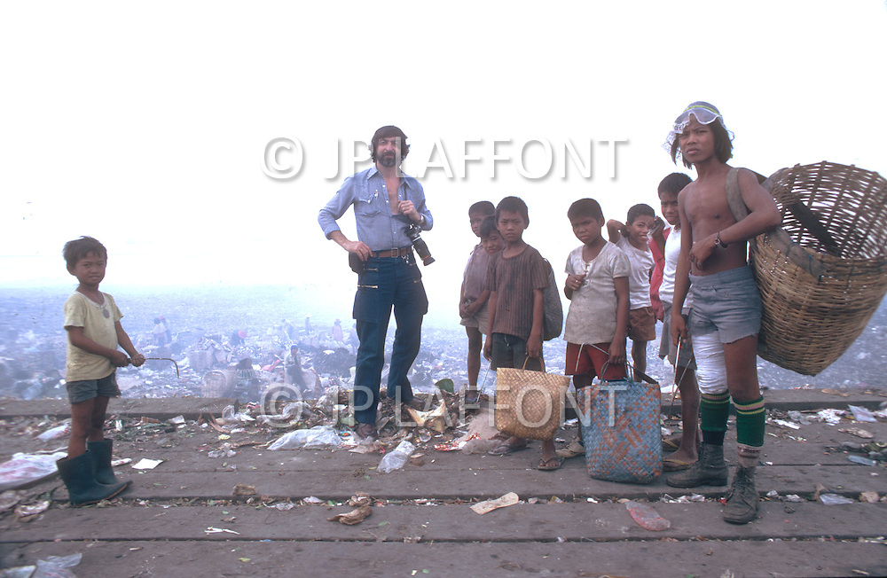 Photographer Jean Pierre Laffont with child garbage collectors at a dump outside of Manila, Philippines - Child labor as seen around the world between 1979 and 1980 - Photographer Jean Pierre Laffont, touched by the suffering of child workers, chronicled their plight in 12 countries over the course of one year.  Laffont was awarded The World Press Award and Madeline Ross Award among many others for his work.