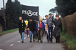 """Young Anarchist Peace Demonstrators march from  Aldermaston to Greenham Common Easter 1983. Peace demonstrators formed a human chain stretching 14 miles. They lined a route along what the protesters call """"Nuclear Valley"""" in Berkshire. The chain started at the American airbase at Greenham Common, passed the Aldermaston nuclear research centre and ended at the ordnance factory in Burghfield."""