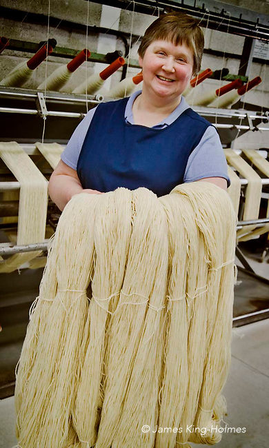 Woman textile worker carries processed organic wool to the washing machines which will remove the inherent grease and lanolin it contains. Photographed at the Natural Fibre Company Ltd, Launceston, UK.
