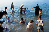 Jordan. Dead sea. Jordanians tourists (men, women and children) take a bath, swimm and float on the salt water. The families enjoy themselves on a sunny friday afternoon. Friday is the day off (resting day) in the arabian culture. The women wear long dresses and a veil on their head as part of muslim tradition and religion. On the other side of the sea is Palestine and the West Bank (Occupied Territories by Israel). © 2002 Didier Ruef