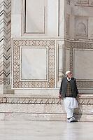 Agra, India.  Taj Mahal. Indian Man Wearing Shoe Covers to Protect Taj Tiles from Scratching.