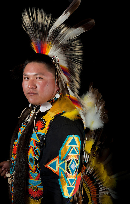 Traditional pow wow dancer, Carlton Yazzie (Dine aka Navajo), dressed in colorful regalia of a roach headdress, beaded vest and eable feather bustle holds a wooden coup stick