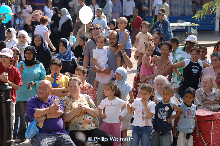 A crowd of children and adults watches stage performances at Church Street Summer Festival 2005, Paddington, London.
