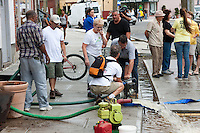 MAMARONECK, NY - AUGUST 28: Residents pump water out of the basement of a small business on Mamaroneck Avenue in the Village of Mamaroneck, New York on Sunday August 28, 2011 in the aftermath of Hurricane Irene.