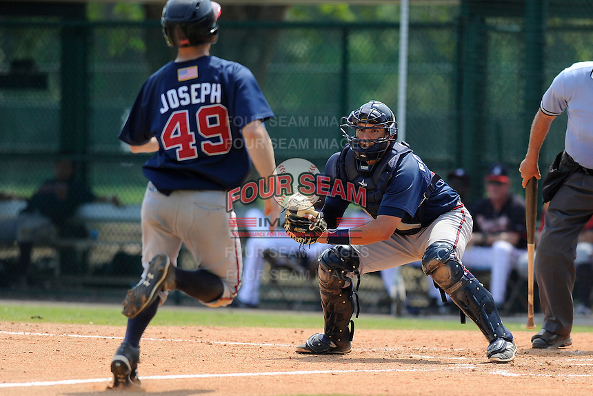 Catcher Steven Rodriguez (12) of the Atlanta Braves farm system has the ball and prepares to tag out Corban Joseph in a Minor League Spring Training intrasquad game on Wednesday, March 18, 2015, at the ESPN Wide World of Sports Complex in Lake Buena Vista, Florida. (Tom Priddy/Four Seam Images)