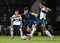 LAKE BUENA VISTA, FL - JULY 26: Graham Smith of Sporting KC and Theo Bair of Vancouver Whitecaps FC challenge for a ball during a game between Vancouver Whitecaps and Sporting Kansas City at ESPN Wide World of Sports on July 26, 2020 in Lake Buena Vista, Florida.