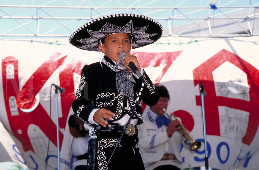 HISPANIC MARIACHI VOCALIST (BOY) SINGING AT CULTURAL FESTIVAL. YOUNG MARIACHI VOCALIST. SAN JOSE CALIFORNIA.
