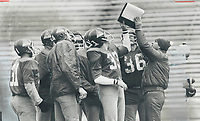 1978<br />  FILE PHOTO - ARCHIVES -<br /> <br /> Alouette special teams coach Larry Pasquale (toque) holds up a playbook for his squad yesterday at Exhibition Stadium<br /> <br /> Bezant, Graham<br /> Picture, 1978, <br /> <br /> NOTE : Retouched <br /> <br /> 1978<br /> <br /> PHOTO : Graham Bezant - Toronto Star Archives - AQP