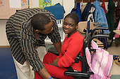 MR / Albany, NY.Langan School at Center for Disability Services .Ungraded private school which serves individuals with multiple disabilities.Teaching assistant (African-American) interacts with child  sitting in a wheelchair. She has severely limited verbal skills. Girl: 10, African-American, cerebral palsy, expressive and receptive language delays.MR: And6; Wes2.© Ellen B. Senisi