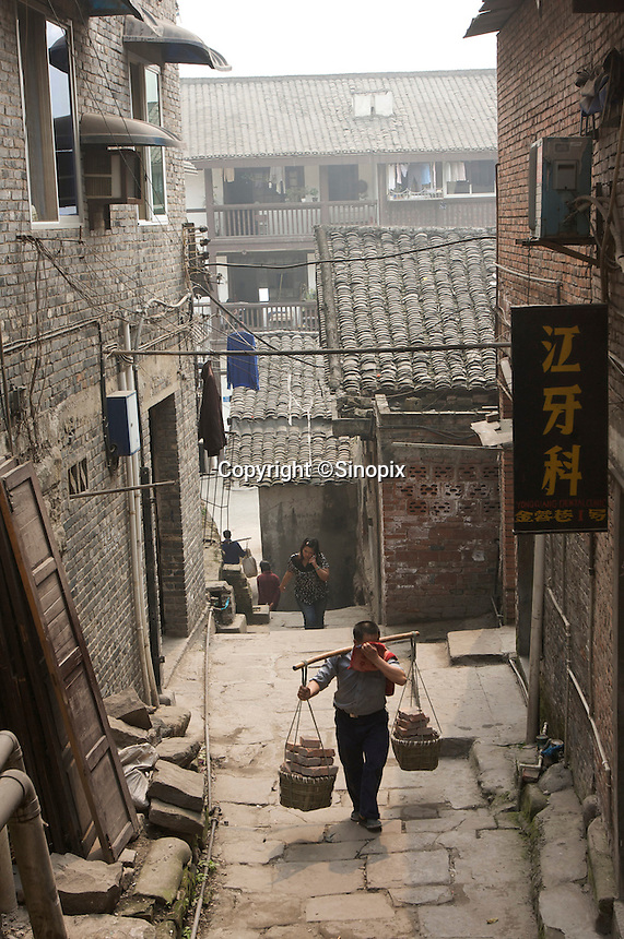 "A porter transports a load of bricks on bamboo poles in Ciqikou, a touristic street where shops sell souvenirs and local snacks in Chongqing, China. The chongqing porters known as the ""stick men"" are famous throughout China..09 Apr 2008"