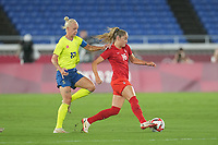 YOKOHAMA, JAPAN - AUGUST 6: Janine Beckie #16 of Canada is marked by Caroline Seger #17 of Sweden during a game between Canada and Sweden at International Stadium Yokohama on August 6, 2021 in Yokohama, Japan.