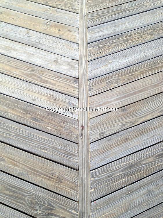 A closeup of the seam of a boardwalk shows its typical herringbone pattern