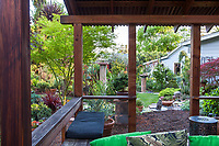 Backyard covered deck outdoor room with built in benches framing California plant collector garden - Carol Brant