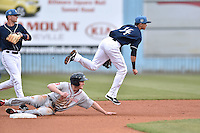 Asheville Tourists shortstop Emerson Jimenez (14) completes the turn on a double play over a hard sliding Derek Miller (16) as Forrest Wall (7) watches on during game one of a double header against the Greenville Drive on April 18, 2015 in Asheville, North Carolina. The Tourists defeated the Drive 2-1. (Tony Farlow/Four Seam Images)