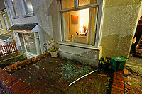 """Pictured: The smashed front window outside the house of Adam Romain in Waun-Wen Road in the Mayhill area of Swansea, Wales, UK. Thursday 20 May 2021<br /> Re: Gangs of """"yobs"""" have been setting fire to cars and rolling them down a hill in Swansea, Wales, UK.<br /> South Wales Police said they attended """"large scale disorder"""" in the Mayhill area of the city on Thursday evening."""