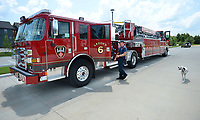 Martin Striefler, a firefighter with the Fayetteville Fire Department, and his dog, Ember, walk Tuesday, July 27, 2021, back to the cab of the Ladder 6 while training on the department's new tiller truck off Hollywood Avenue. The department bought its first tiller truck for $1.4 million using money from its share of city sales tax revenue. Early voting starts Tuesday, and Election Day is Aug. 10, to continue the 1-cent tax for operations and some capital expenditures. Visit nwaonline.com/210728Daily/ for today's photo gallery.<br /> (NWA Democrat-Gazette/Andy Shupe)