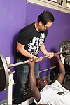 Education High School male students using weight room mentored by male teacher