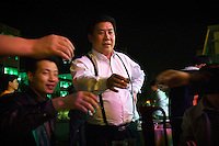 Bosses from a jeans production factory raise a toast, 'To the millionaires of Zhongshan'.