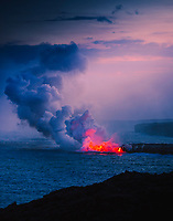 Evening view of glowing lava entering the sea at the Kamokuna entry point, Hawai'i Volcanoes National Park, Hawai'i Island.