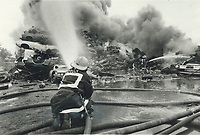 1986 FILE PHOTO - ARCHIVES -<br /> <br /> Wrecking yard catches fire. Firemen turn their nozzles on a 30-metre (100-foot) pile of tires that caught fire yesterday and sent up a large plume of black smoke. The fire started at an auto wreckers yard north of Queen St. in Etobicoke. No one was injured in the blaze. Traffic was tied up along the Queensway and Highway 427.<br /> <br /> 1986<br /> <br /> PHOTO :  Erin Comb - Toronto Star Archives - AQP