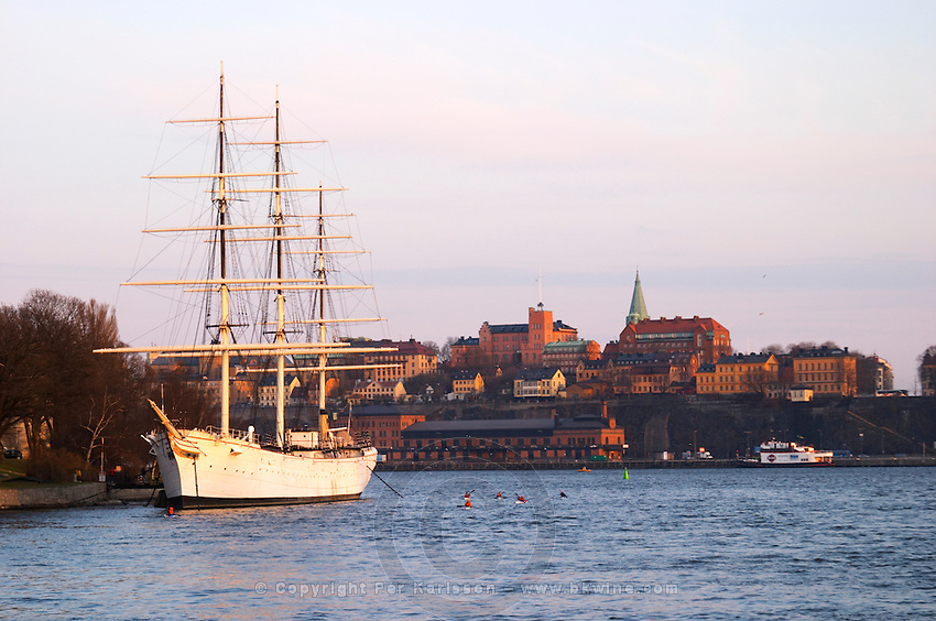 The Af Chapman three masted former school tall ship, now anchored off Skeppsholmen and functioning as a youth hostel. Sodermalm in background. Stockholm. Sweden, Europe.
