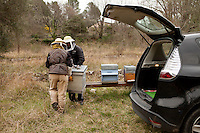 Beekeeper Amanda Dowd and her helper carry beehives to their final destination after transhumance; a field below the village of Pont du Loup, Alpes Maritimes, France, 18 February 2014. Here the bees will be able to take advantage of the spring flowers already in bloom at lower altitudes before Asian hornets start to prey on the hives in the summer.