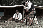 French Voyageur canoe camp in the woods greeted by a visitor