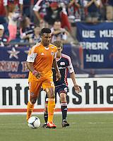 Houston Dynamo midfielder Giles Barnes (23) passes the ball as New England Revolution midfielder Scott Caldwell (6) defends. In a Major League Soccer (MLS) match, Houston Dynamo (orange) defeated the New England Revolution (blue), 2-1, at Gillette Stadium on July 13, 2013.