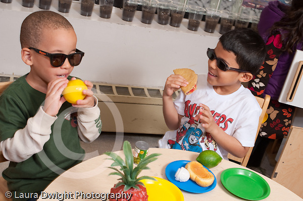 Education Preschool 3-5 year olds pretend play in kitchen area two boys in dark glasses eating play food