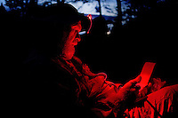 Photo story of Philmont Scout Ranch in Cimarron, New Mexico, taken during a Boy Scout Troop backpack trip in the summer of 2013. Photo is part of a comprehensive picture package which shows in-depth photography of a BSA Ventures crew on a trek.  In this photo BSA Venture Crew adult advisor writes in his journal under the light of his headlamp in the backcountry at Philmont Scout Ranch.   <br /> <br /> The  Photo by travel photograph: PatrickschneiderPhoto.com