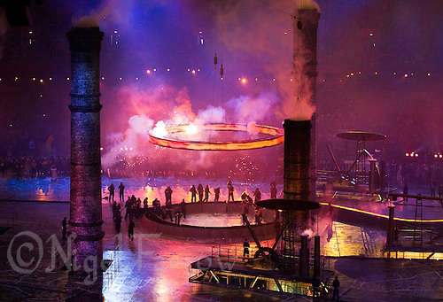 """27 JUL 2012 - LONDON, GBR - An iron ring begins to rise to join four others above the stadium to form the Olympic symbol during the """"Pandemonium"""" section of the Opening Ceremony of the London 2012 Olympic Games in the Olympic Stadium in the Olympic Park, Stratford, London, Great Britain (PHOTO (C) 2012 NIGEL FARROW)"""