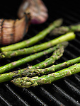 Close up of asparagus and red onion on barbecue grill