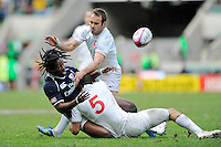 Justin Boyd of the United States offloads as he is tackled by Paul Albaladejo and Renaud Delmas of France (right) during the iRB Marriott London Sevens at Twickenham on Sunday 13th May 2012 (Photo by Rob Munro)