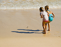 Two girls on Bellows Beach keep their distance from a crab on the defense.