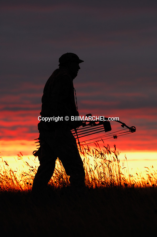00105-039.19 Bowhunting (DIGITAL) Archer is silhouetted against colorful sky at the magic hour.  Color, drama.  V6R1