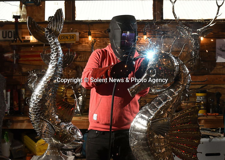Pictured:  Sculptor Michael Turner working on his latest creations, mig welding parts to a five and a half foot tall metal seahorse.<br /> <br /> Metal sculptor Michael Turner has found enquires for his services have increased by 60% during the lockdown period as people have focus on improving their garden and interior spaces around the home.<br /> <br /> The sculptor who has been busy throughout lockdown from his Lymington workshop in the New Forest, Hampshire believes the increase could be down to those who are usually able to treat themselves by going out, but are now looking to spend their money on items to improve their lockdown experience and surroundings.<br /> <br /> © Simon Czapp/Solent News & Photo Agency<br /> UK +44 (0) 2380 458800