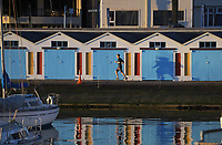 A runner runs past the boat sheds on Oriental Parade at 7.30am, Friday during Level 4 lockdown for the COVID-19 pandemic in Wellington, New Zealand on Friday, 20 August 2021.