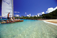 Group of young people catamaran sailing off Waimea Bay, North shore on the Island of Oahu