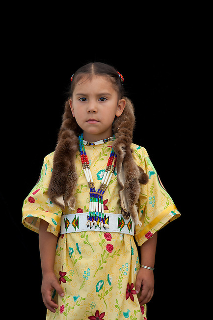 Little Native American girl poses next to black backdrop. 4 year old Cedar Davis (Shoshone) wearing a traditional wing dress, beaded belt and otter wraps.