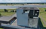Foto: VidiPhoto<br /> <br /> DODEWAARD – Specialisten werken dinsdag aan de buitenzijde van het reactorgebouw van de voormalige kerncentrale in Dodewaard. Bij werkzaamheden aan het dak vloog op 21 mei de isolatielaag tussen de beplating  en de 60 cm. dikke betonnnen wand aan de zuidgevel in brand. De beplating wordt op dit moment vervangen door niet-asbesthoudende panelen. De herstelwerkzaamheden worden gecombineerd met groot onderhoud aan de noordgevel. In totaal gaat het om bijna 1400 m2 nieuw plaatwerk. Omdat pas in 2045 de radioactieve straling bij de kernreactor laag genoeg is om de gebouwen te kunnen slopen, moet het complex tot die tijd in optimale conditie blijven. Voor het onderhoud van de kerncentrale tot 2045 is 19 miljoen euro gereserveerd. De werkzaamheden aan de kerncentrale in ruste duren tot ongeveer half augustus. Uitvoerder is de firma Robertson uit Lelystad.