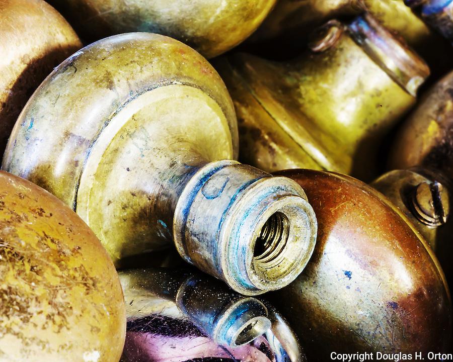 Vintage door knobs stacked in bin.